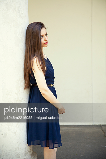 Woman in Blue Summer Dress Leaning Against Pillar  - p1248m2216085 by miguel sobreira