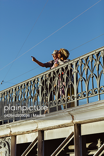 Senior man pointing while standing by woman on bridge against blue sky - p426m2239036 by Maskot