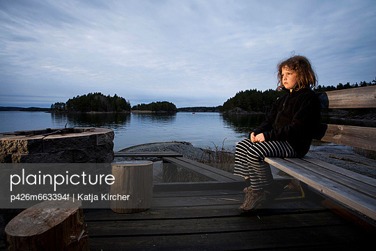 Young girl sitting on wood bench at lakeside while looking away