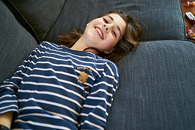 From above girl smiling while resting on soft couch at home - p1166m2201431 by Cavan Images