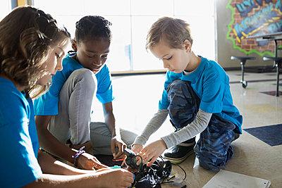 Pre-adolescent students assembling robotics on classroom floor - p1192m1231086 by Hero Images