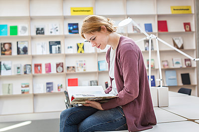 Studentin blättert in einem Buch in der Bibliothek - p1284m1452031 von Ritzmann