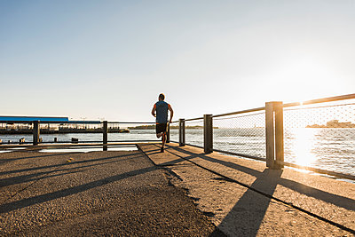 USA, Brooklyn, back view of man jogging at evening twilight - p300m1206212 by Uwe Umstätter