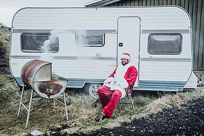 Iceland, Santa Claus sitting in front of caravan barbecueing - p300m2081049 von Oscar Carrascosa Martinez