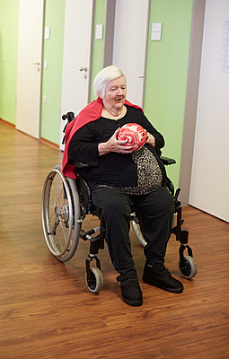 Age demented senior woman bowling with foam ball in a nursing home - p300m2219189 by Heinz Linke