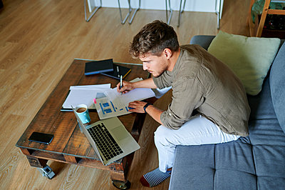 Male entrepreneur writing on paper while sitting with laptop at home - p300m2241204 by Kiko Jimenez
