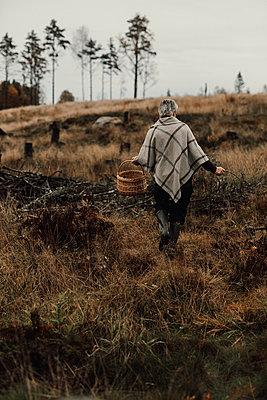 Woman walking through autumn meadow - p312m2191021 by Jennifer Nilsson