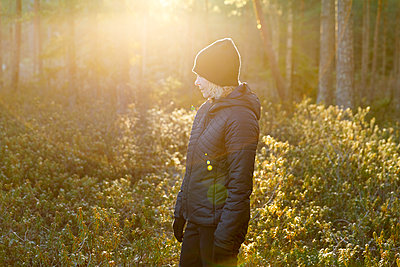 Woman wearing black in sunlit forest - p352m2120183 by Åke Nyqvist