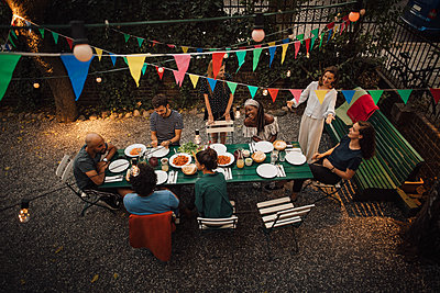 High angle view of multi-ethnic friends enjoying dinner at table during garden party - p426m2046201 by Maskot