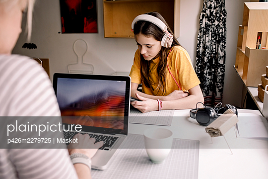 Girl wearing headphone E-learning through digital tablet while sitting with businesswoman working on laptop at desk - p426m2279725 by Maskot