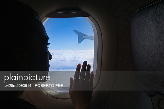 Woman travelling in airplane, looking out window - p429m2090614 by ROBERTO PERI