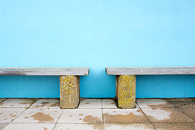 Two wooden bench seats against blue wall - p1057m1586853 by Stephen Shepherd
