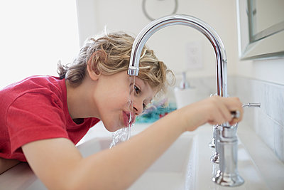 Boy drinking water from bathroom faucet - p1192m1107747f by Hero Images