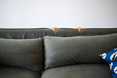 Boy hiding behind sofa - p1640m2254825 by Holly & John