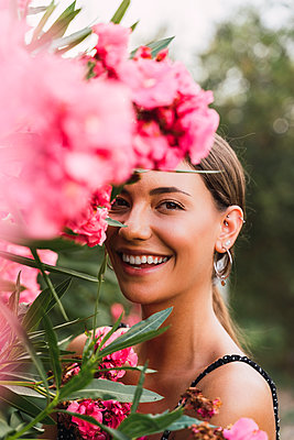 Portrait of laughing young woman in a park with pink blossoming flowers - p300m2143350 von VITTA GALLERY