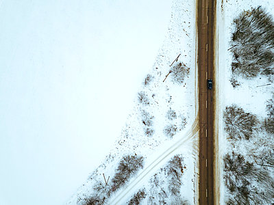 Russia, Moscow Oblast, Aerial view of countryside highway cutting through snow-covered landscape - p300m2171123 by Konstantin Trubavin