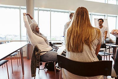 Smiling bored woman with arms raised looking at friends in classroom - p426m2072295 by Kentaroo Tryman