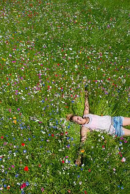 Junge Frau in einer Blumenwiese III - p427m917318 von Ralf Mohr
