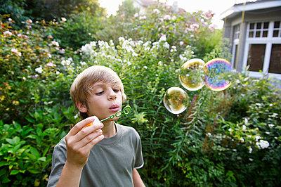 Boy blowing bubbles - p4294957f by Ghislain & Marie David de Lossy