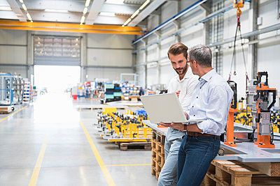 Two engineers with laptop talking in engineering factory - p924m1468803 by Daniel Ingold