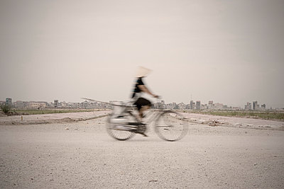 Vietnamese woman rides her bicycle along a deserted construction site road with the city in the distance. Vietnam, Asia. - p934m832750 by Matthew Dakin