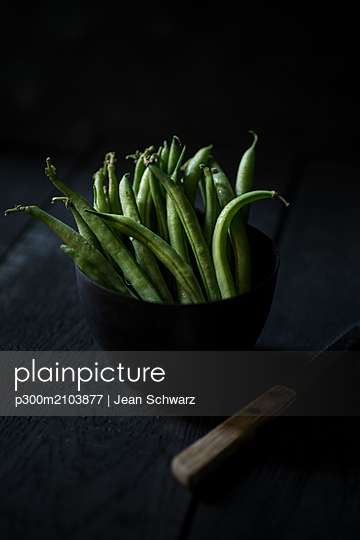 Green beans in black bowl on black wood - p300m2103877 by Jean Schwarz