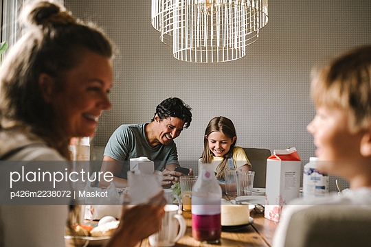 Happy father and daughter using smart phone at dining table - p426m2238072 by Maskot