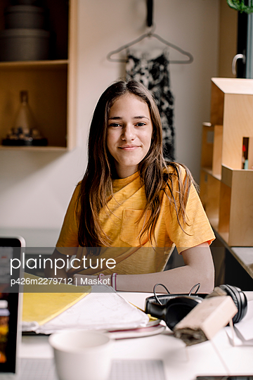 Portrait of smiling girl with long hair sitting at desk - p426m2279712 by Maskot