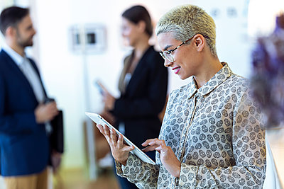 Businesswoman using tablet in office with colleagues in background - p300m2160182 von Josep Suria
