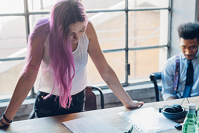 Young woman with pink hair leaning on table in loft office - p300m2202806 by Eugenio Marongiu