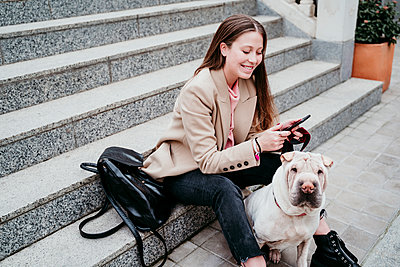 Beautiful woman with Shar-Pei dog using mobile phone while sitting on staircase - p300m2281645 by Eva Blanco