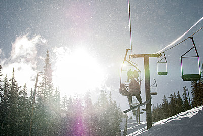 Silverton, Colorado -  snowboarder sitting on a ski lift while backlit by the early morning sunlight. - p343m1218114 by Jon Paciaroni