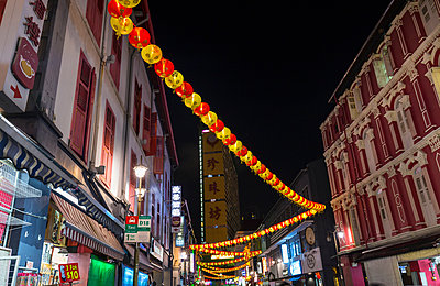 Paper lanterns and shopfronts in chinatown street at night, Singapore, South East Asia - p429m1494158 by Henglein and Steets