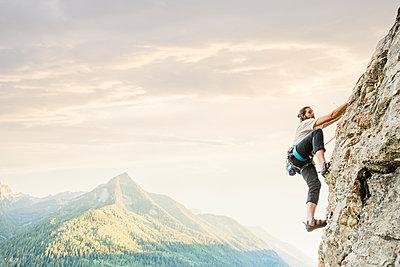 Caucasian man rock climbing - p555m1302109 by Mike Kemp