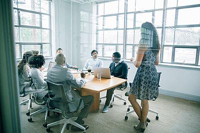 Businesswoman talking behind window in meeting - p555m1504075 by John Fedele