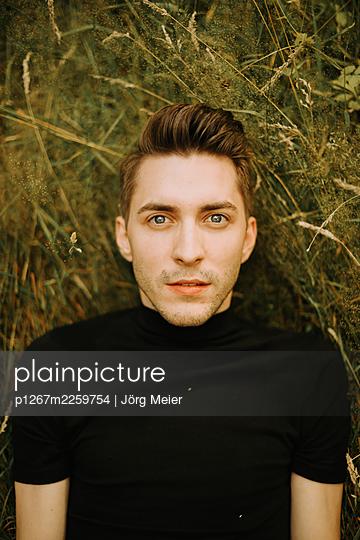 Young man lying on grass - p1267m2259754 by Jörg Meier