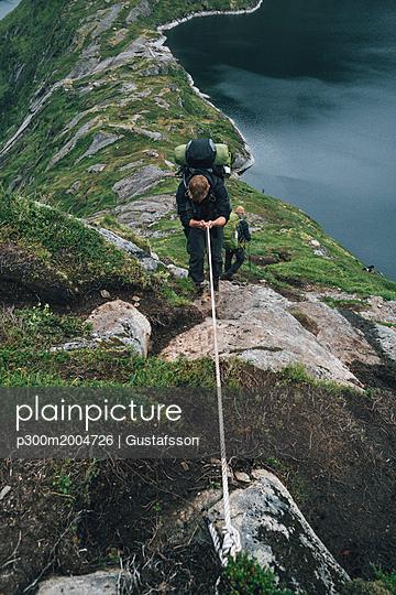 Norway, Lofoten, Moskenesoy,  Group of young men hiking at Vinstad - p300m2004726 von Gustafsson