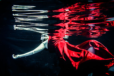 Woman in red dress floating underwater - p1019m1461904 by Stephen Carroll