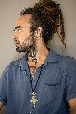 Young man with pigtail and lots of tattoos - p1640m2242081 by Holly & John