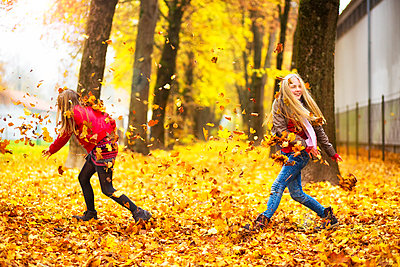 Two girls playing with autumn leaves - p300m1205863 by Roman Märzinger