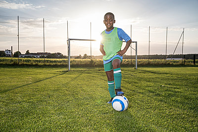 Portrait of confident young football player with ball on football ground - p300m1581196 by Fotoagentur WESTEND61