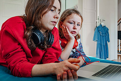 Portrait of two sisters with headphones and laptop on bed - p300m2181055 by Oxana Guryanova