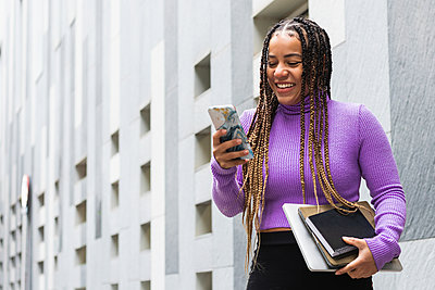 Smiling woman with books using smart phone while standing against gray wall - p300m2267882 by NOVELLIMAGE
