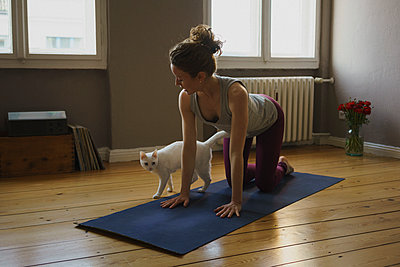 Full length of woman practicing cow pose on exercise mat by cat at home - p301m1579781 by Halfdark