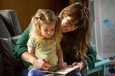 Caucasian mother and daughter reading book on sofa - p555m1311940 by Steve Smith