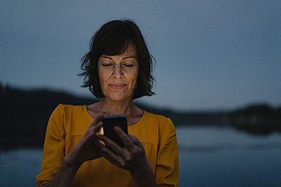 Mature woman using smartphone at night - p586m2109106 by Kniel Synnatzschke