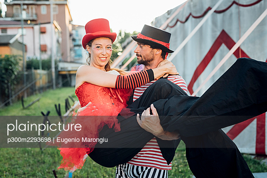 Male acrobat carrying female performer while standing outside circus tent - p300m2293698 by Eugenio Marongiu