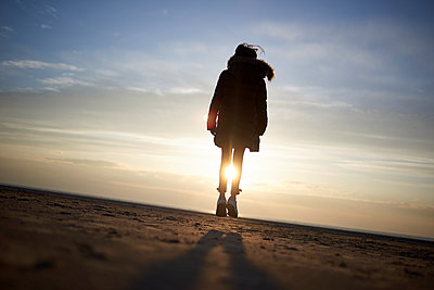 Silhouette girl standing at beach against sky during sunset - p1166m1416335 by Cavan Images