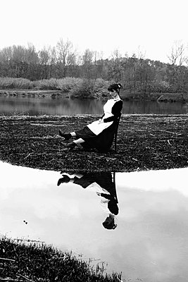 Chambermaid on a chiar by the lake - p1521m2193363 by Charlotte Zobel
