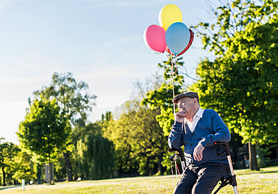 Pensive senior man with balloons sitting on his wheeled walker in nature - p300m1460145 by Uwe Umstätter